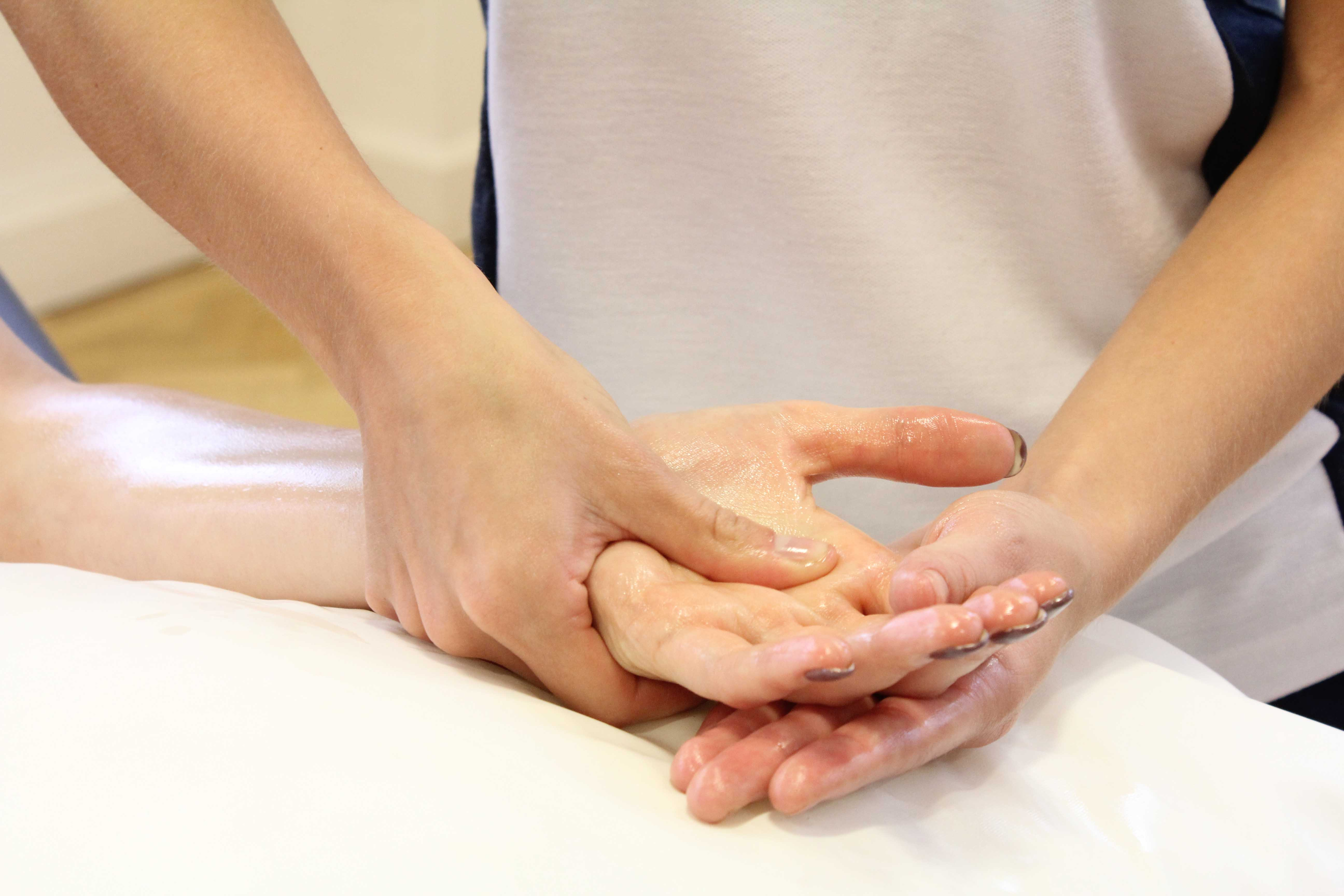 Therapist soft tissue massage of the metacarpals and connective tissues in the hand