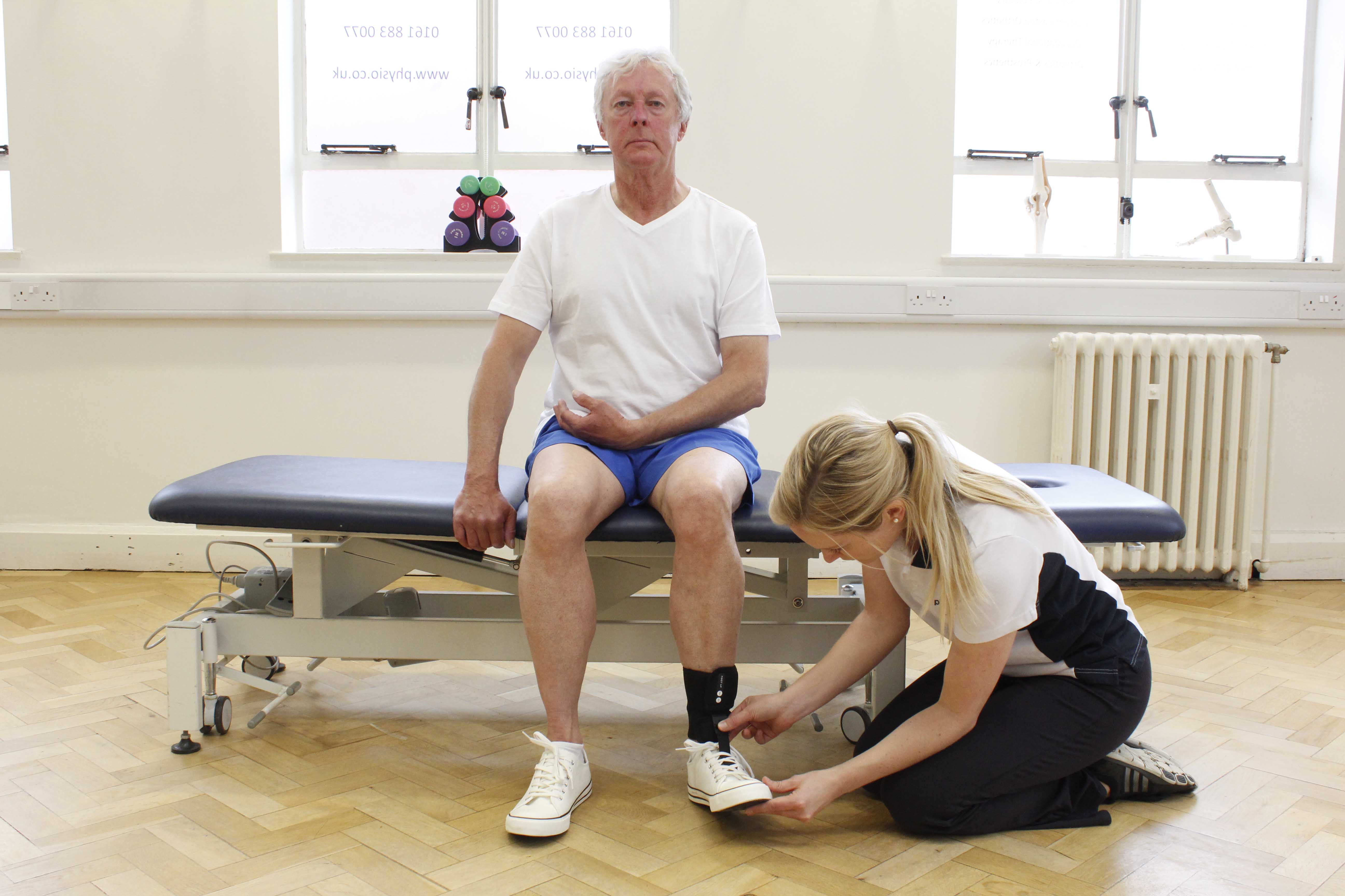 Therapist fitting an ankle splint to support the ankle and prevent foot drop