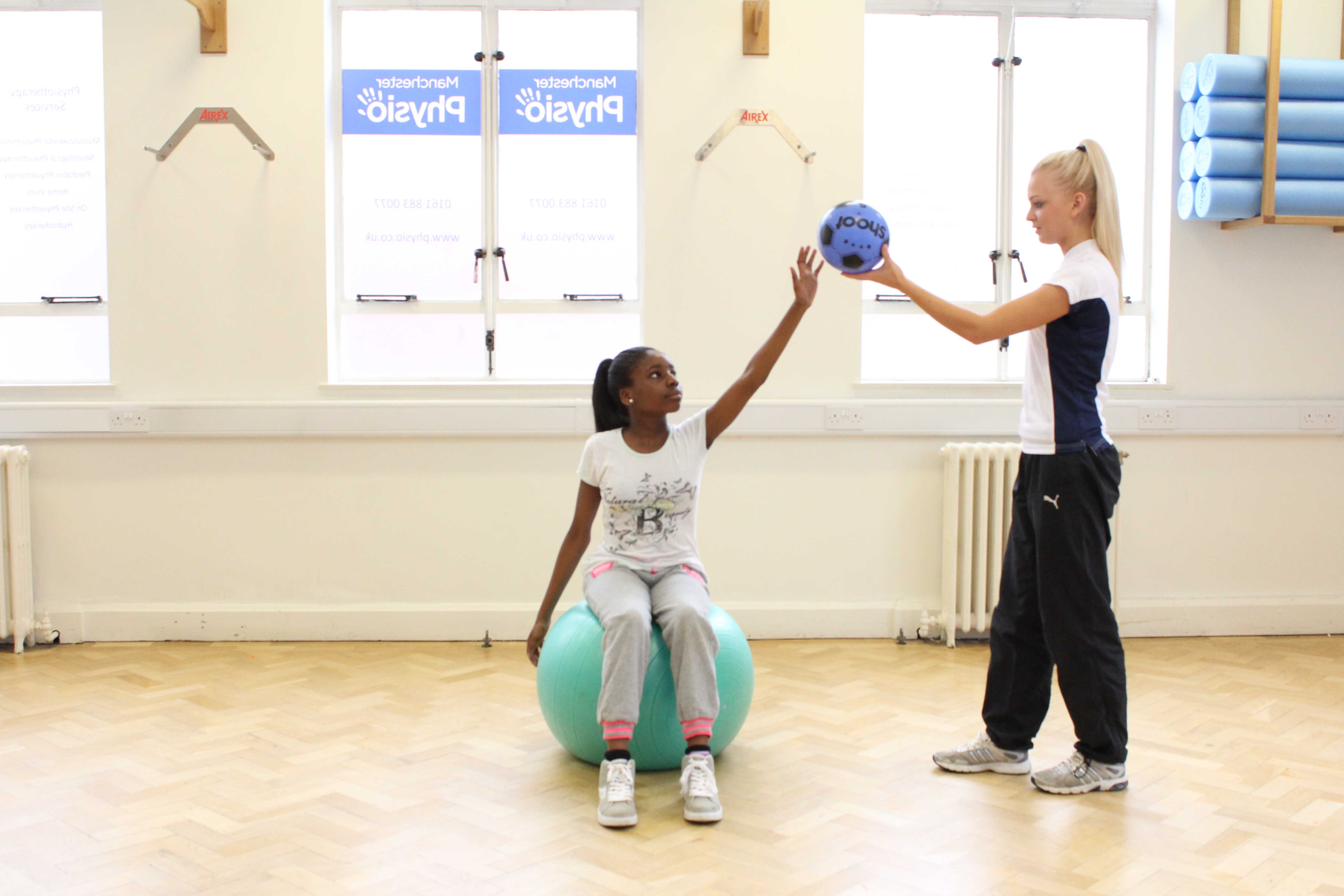 Our physiotherapist challenging a childs balance whilst incorporting fun activities within the session