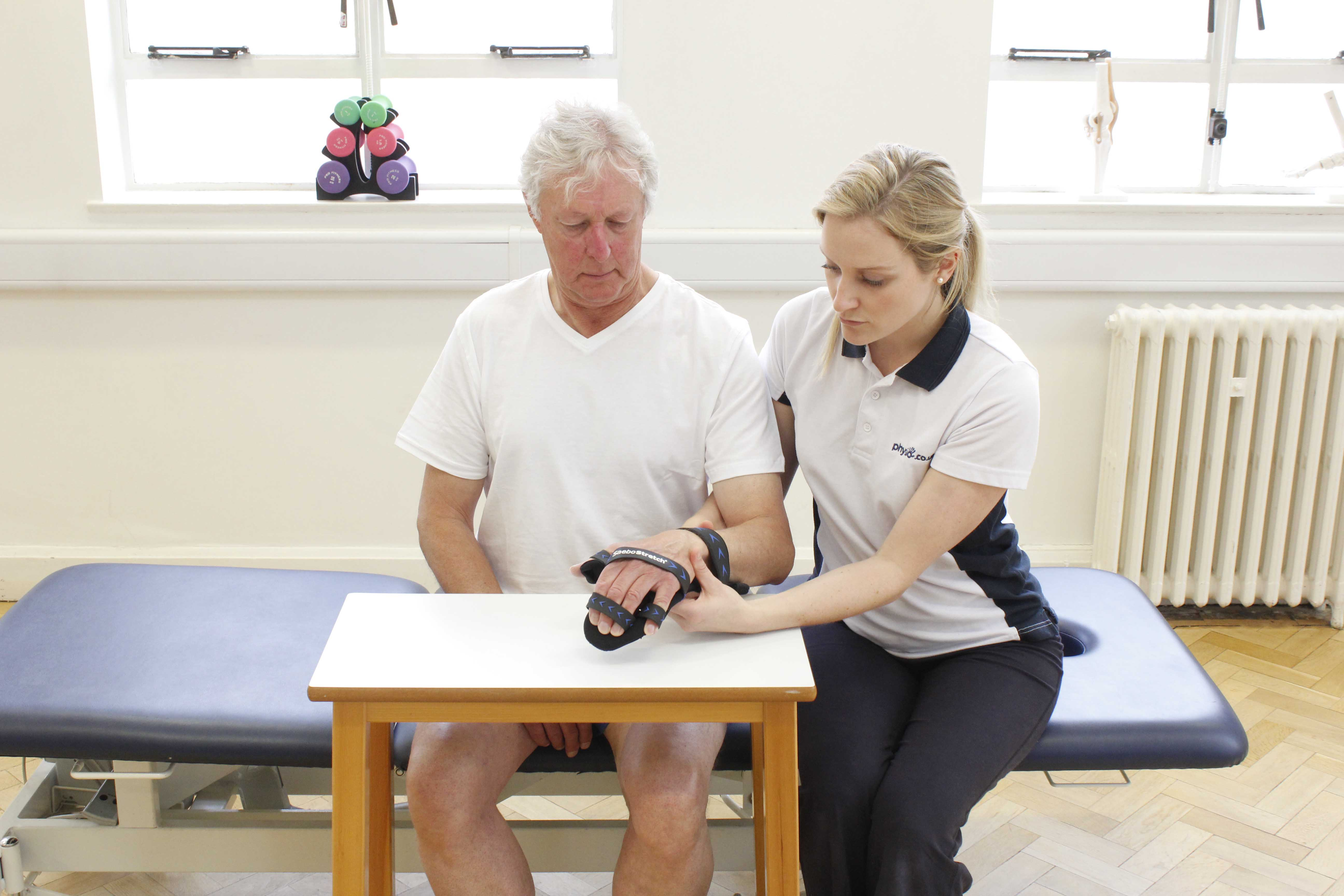 Physiotherapist fitting a wrist splint to prevent muscle and soft tissue shortening in an imobile
