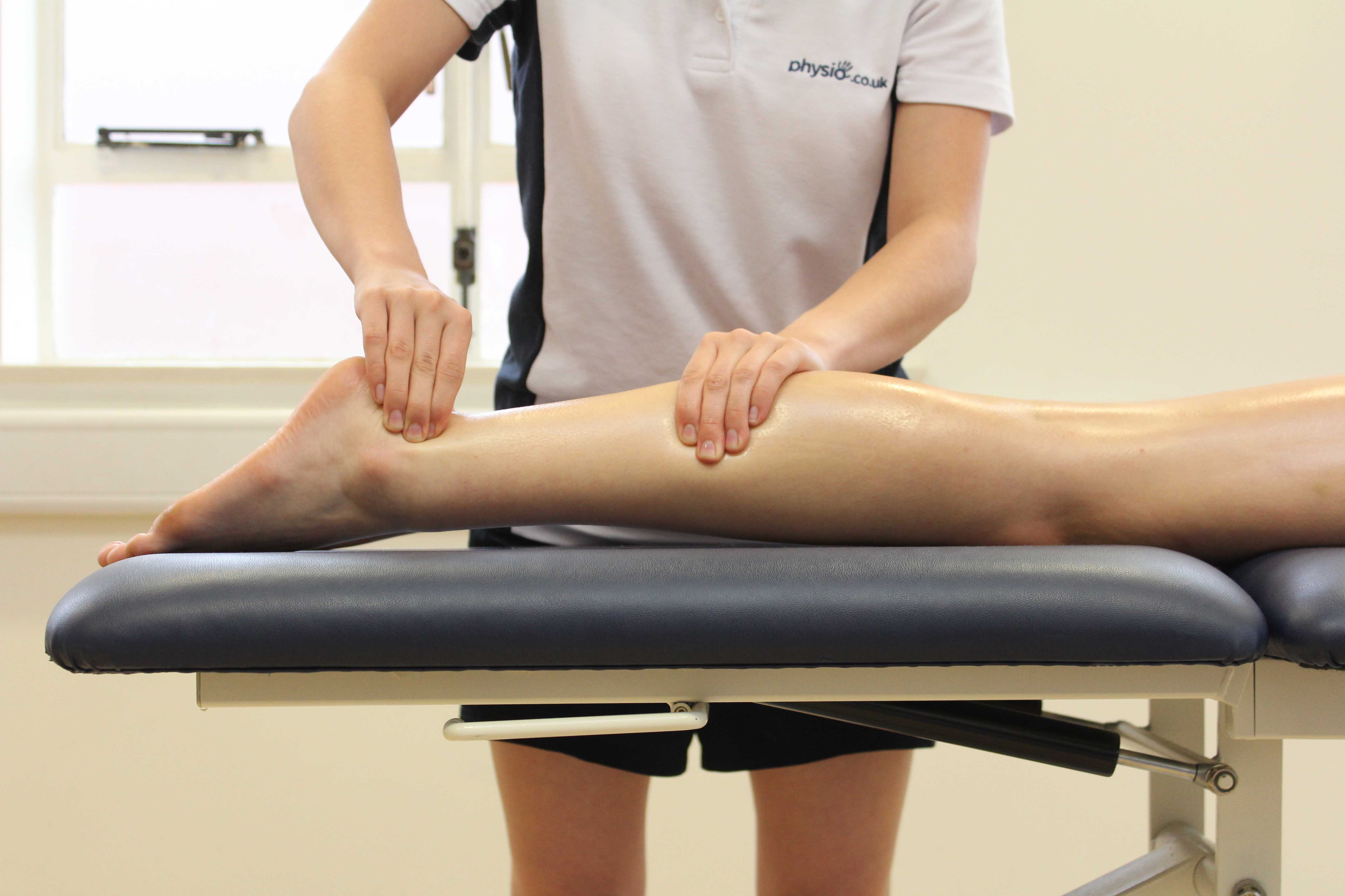 Soft tissue massage of the achilles tendon by experienced physiotherapist