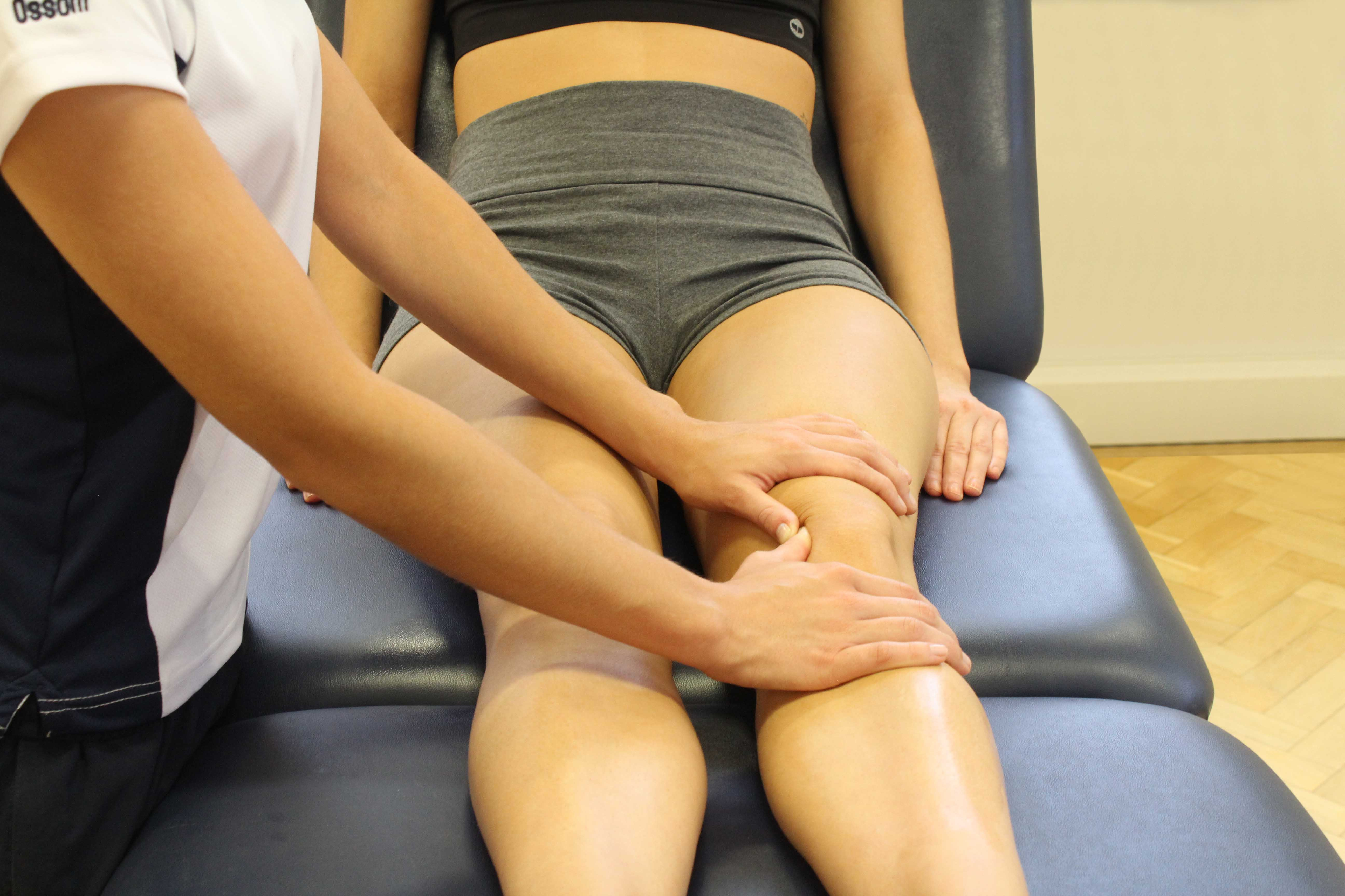 Therapist performing soft tissue massage on the patella and surrounding connective tissue.