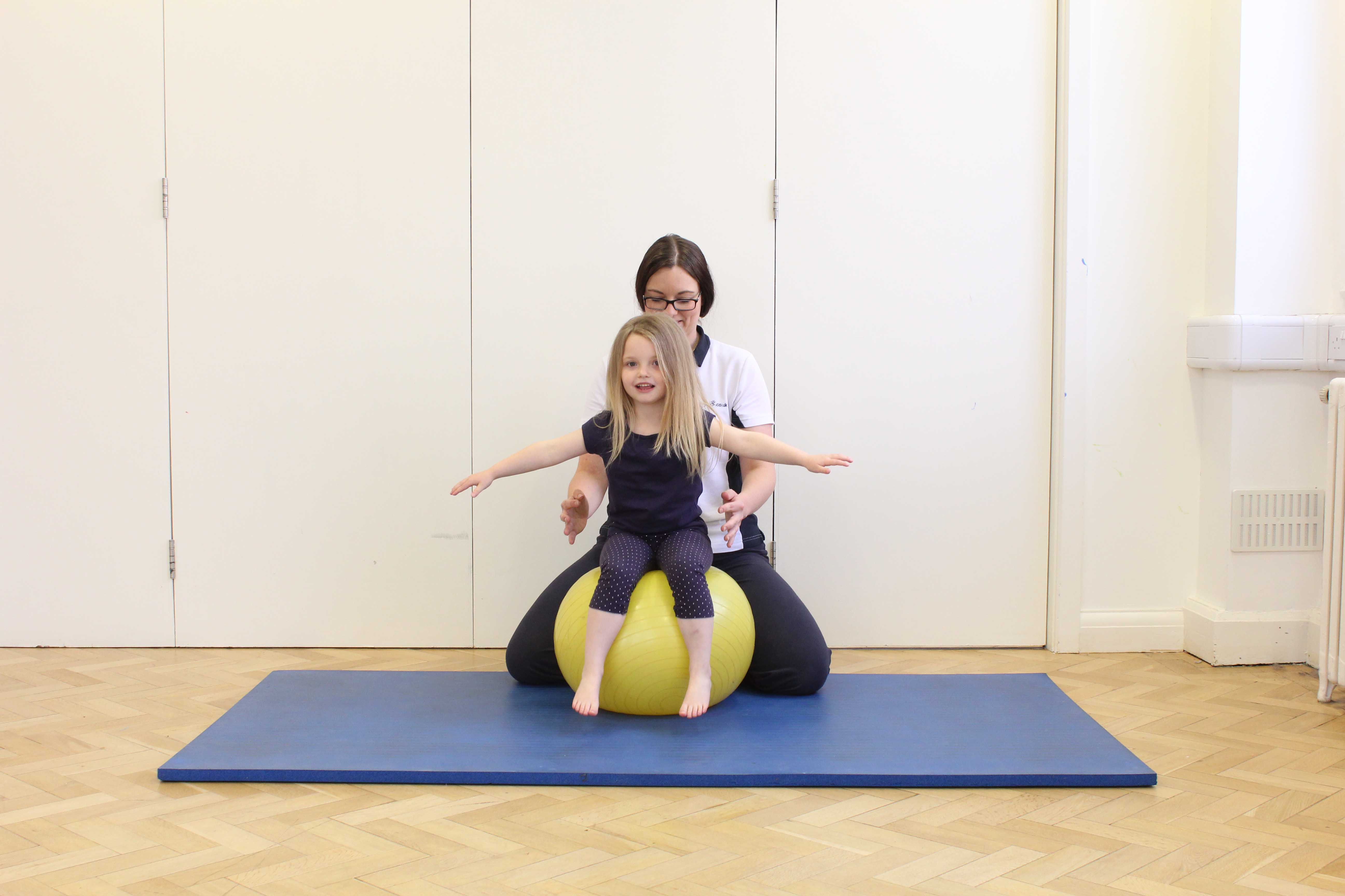 Trainig sitting balance and core stability on a gym ball under close supervision of a paediatric physiotherapist