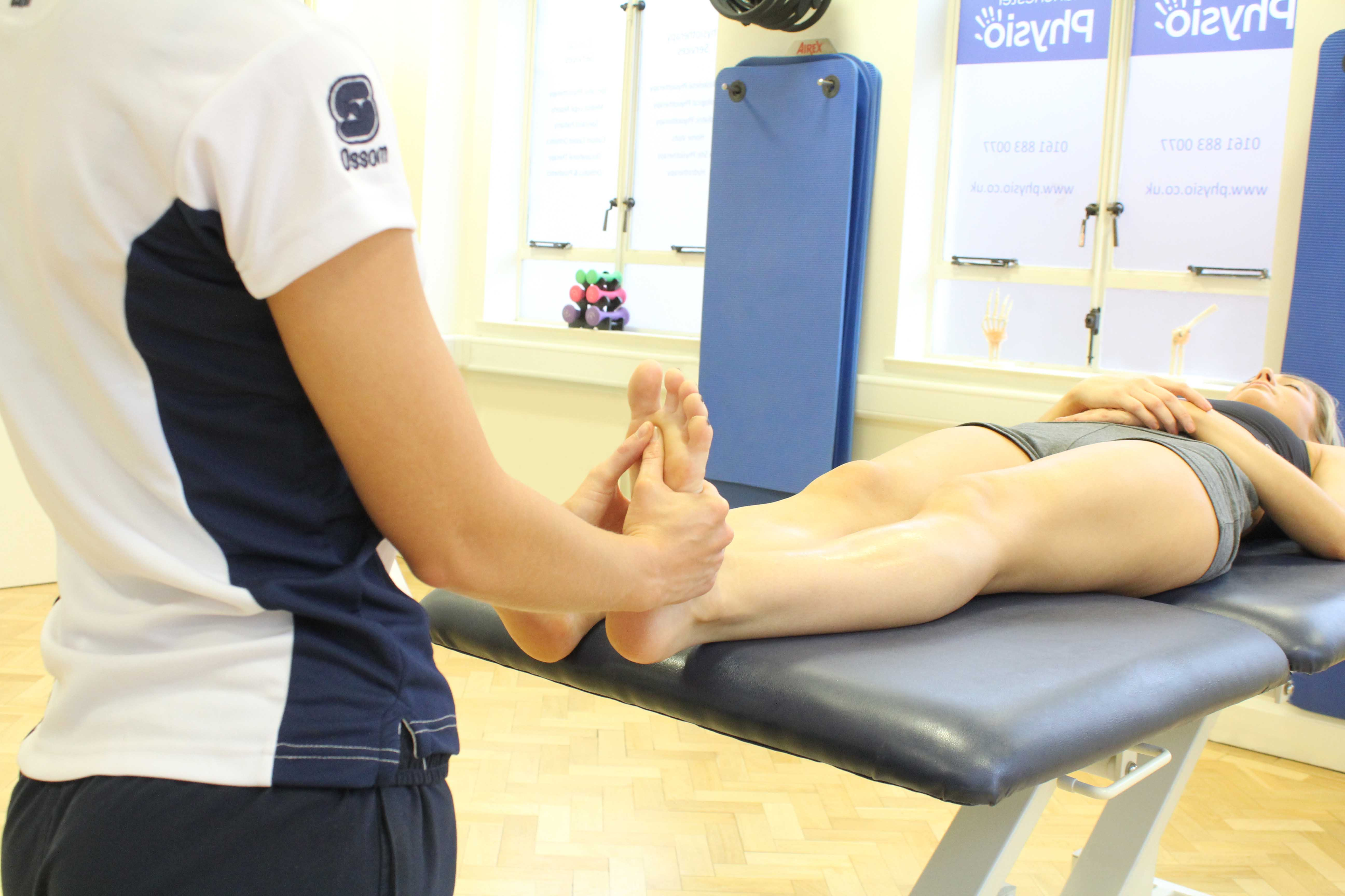 Physiotherapist applying massage to the planta fascia of the foot