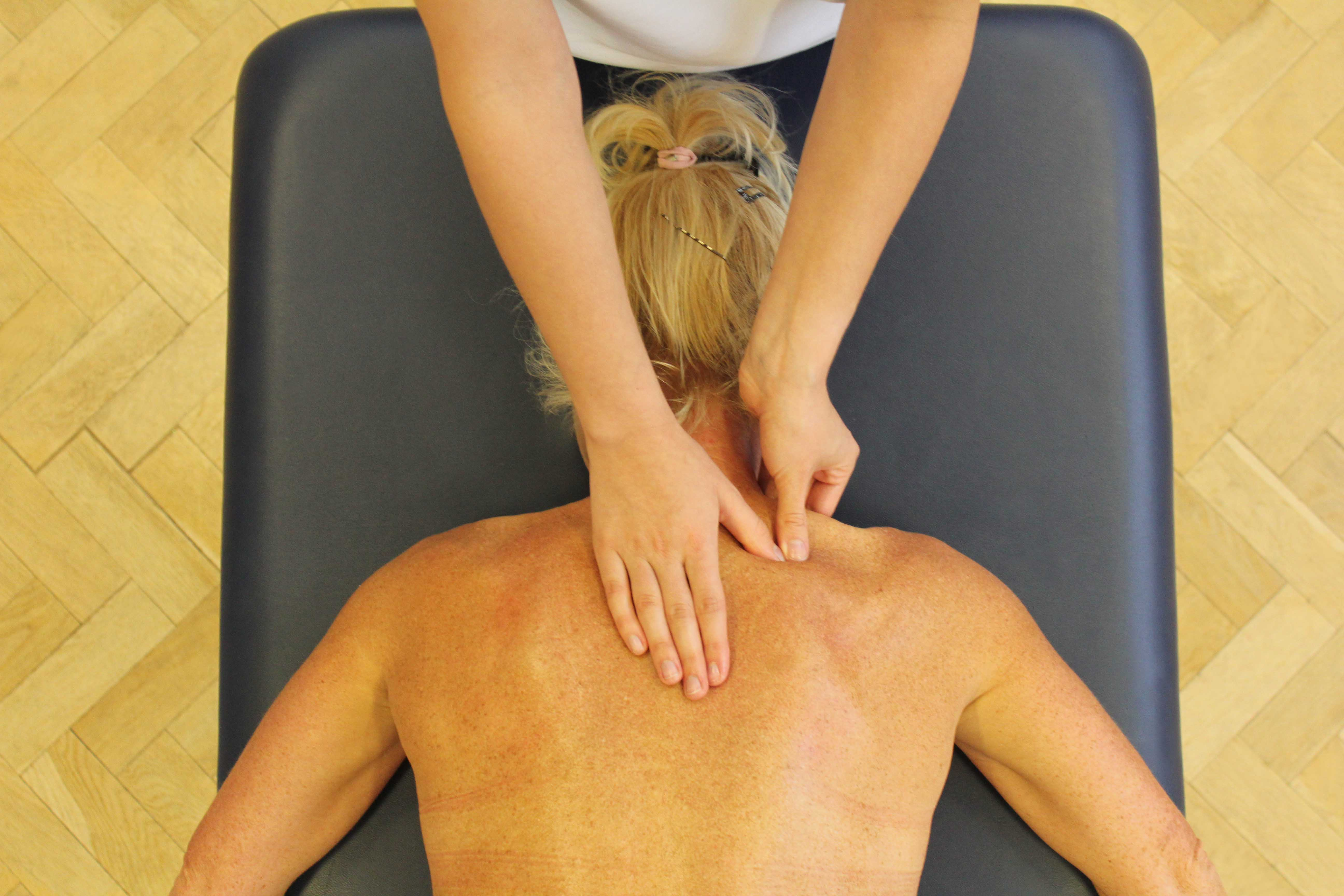 Trigger point massage of the trapezius muscle by a therapist