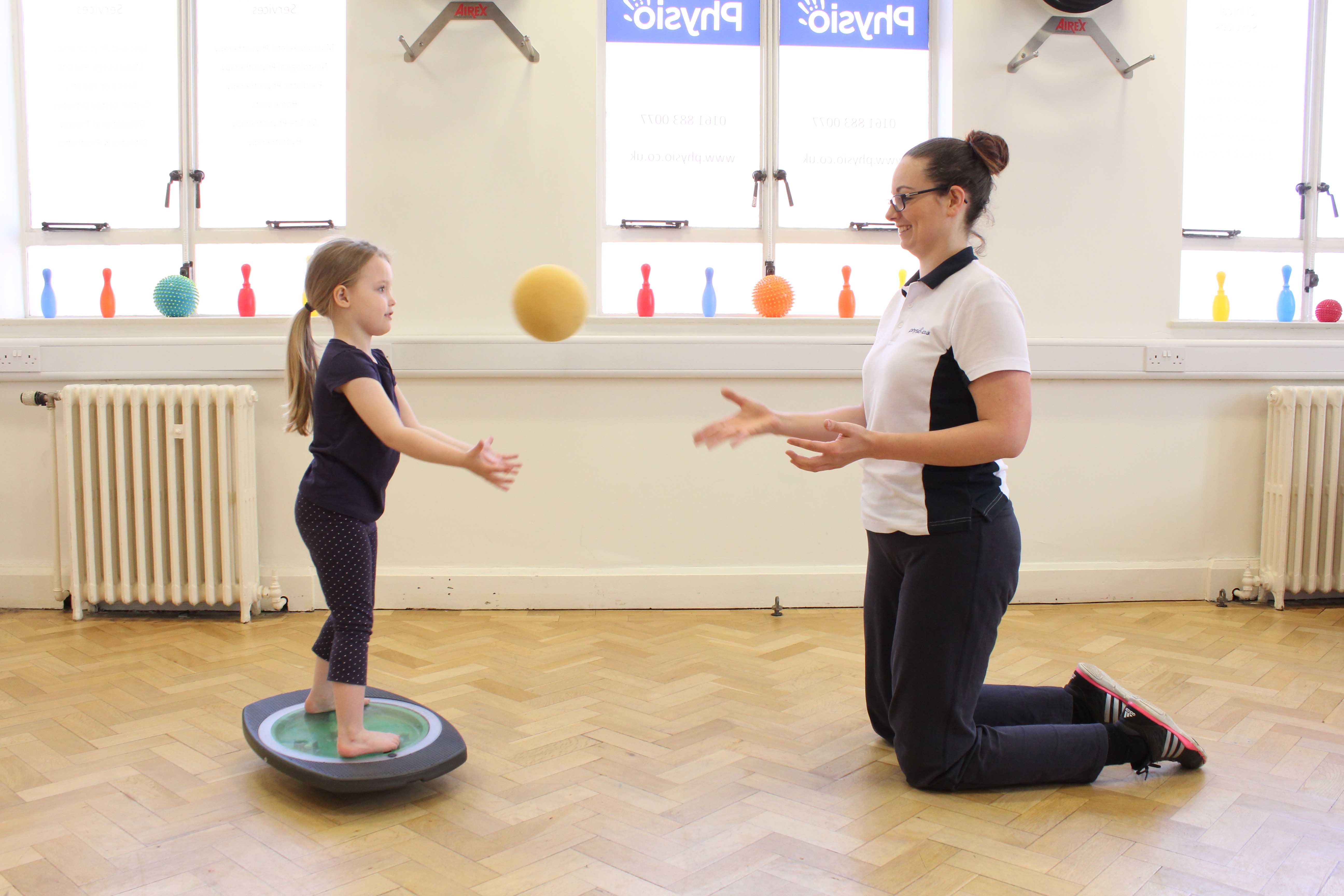 Balance training using a wobble board and ball with assistance from a paediatric neuro physiotherapist