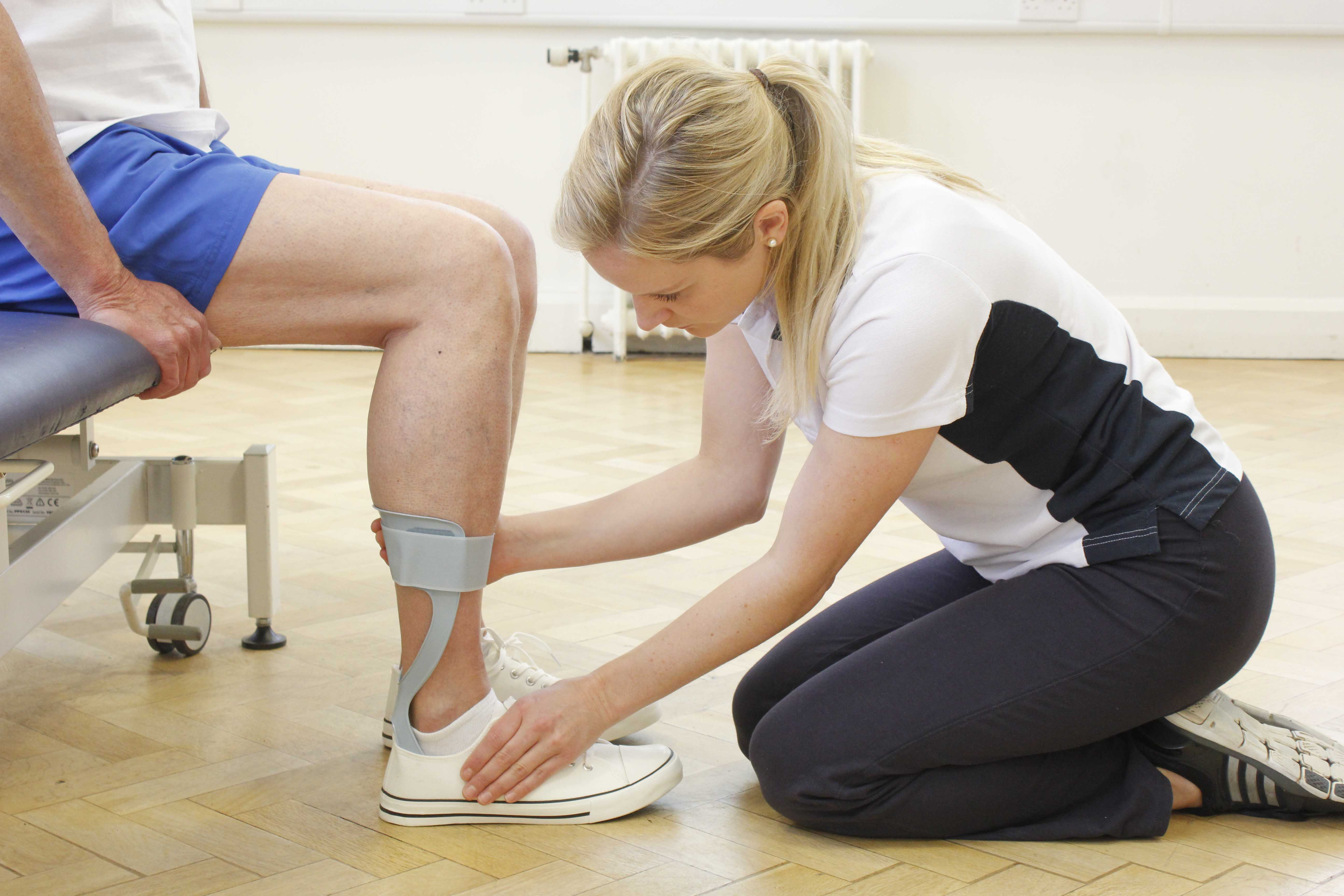 Specialist Physiotherapist using an orthotic to stabilise the ankle during mobilisation
