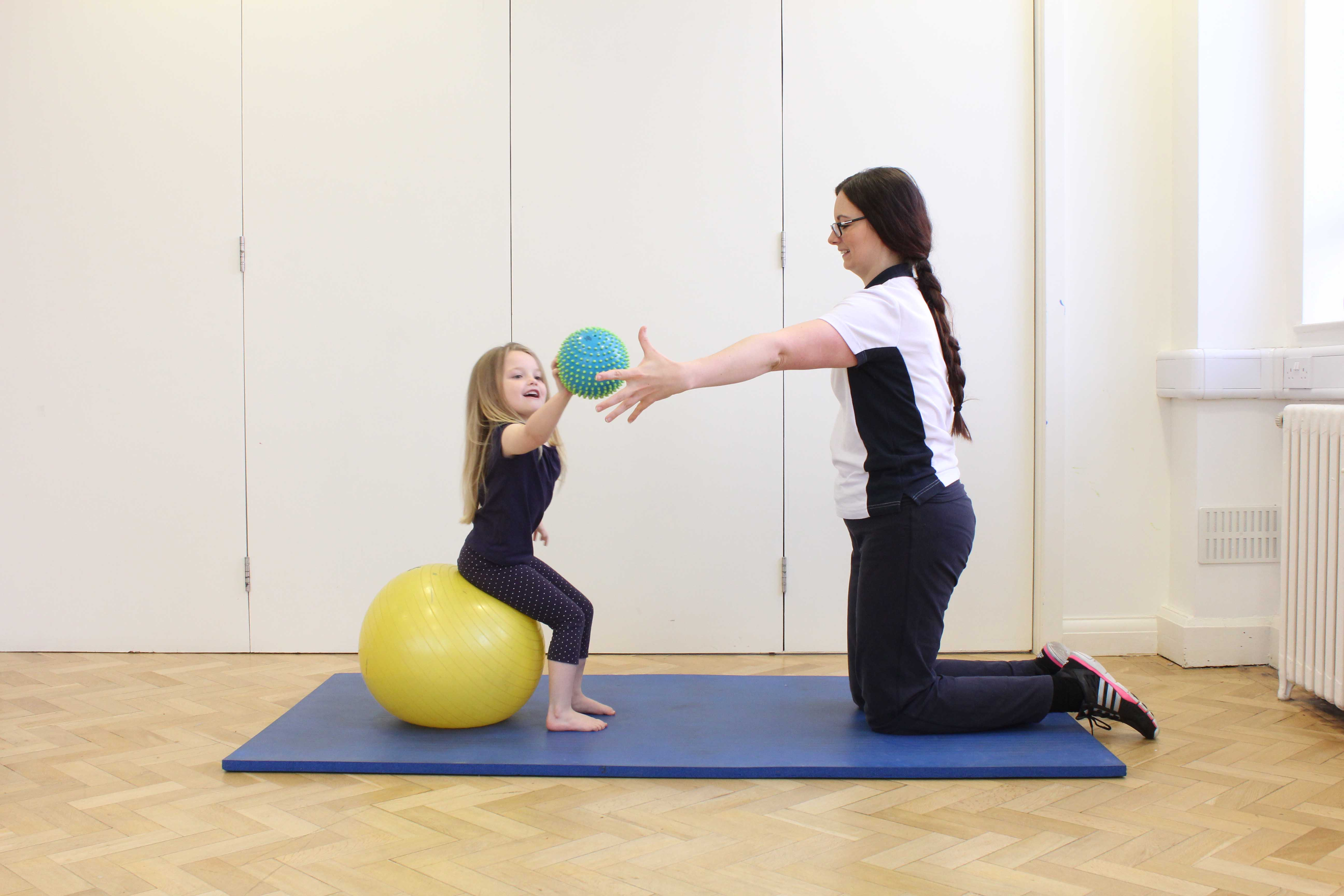 Physiotherapist encouraging increased range of movement with a reaching game.