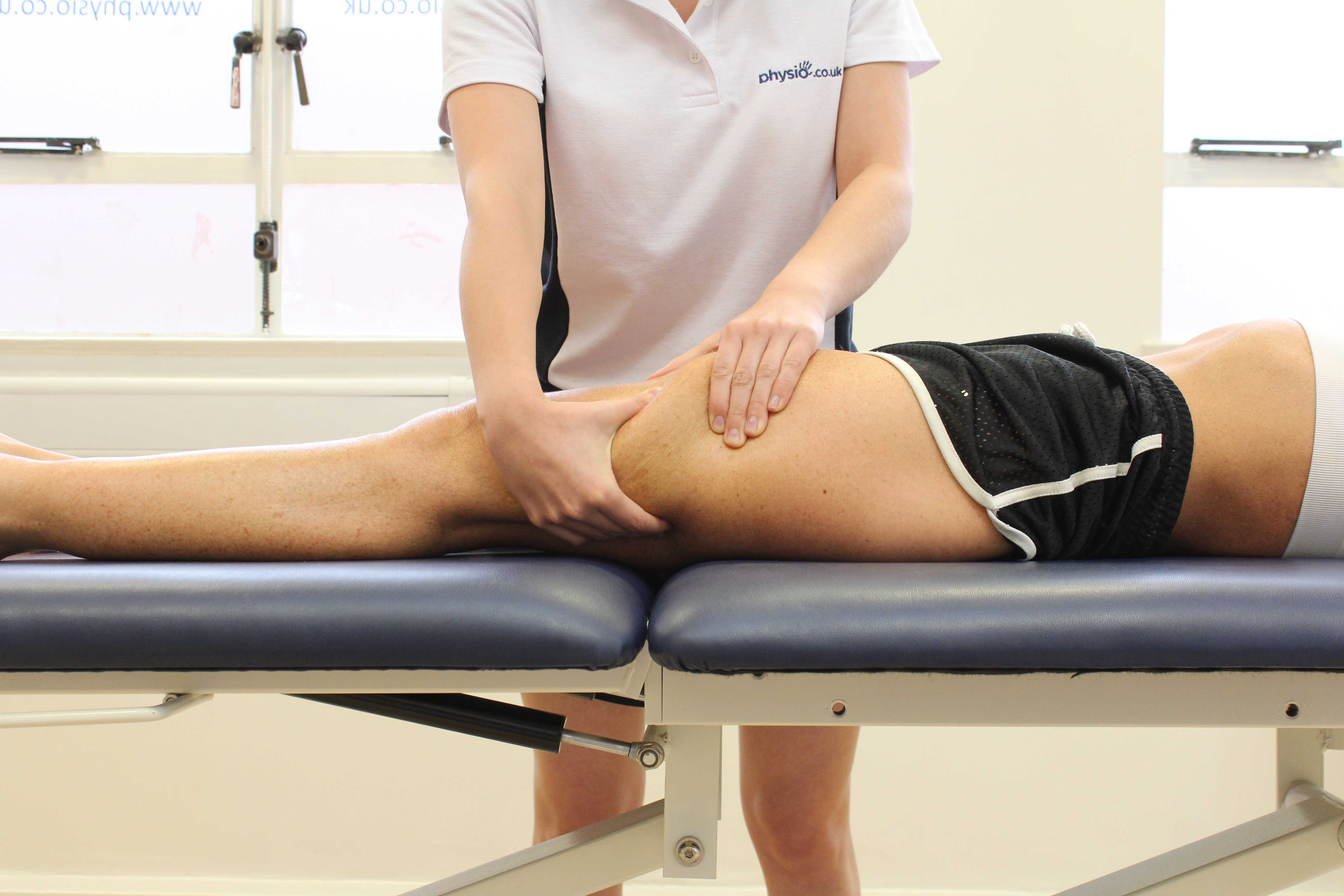 Rolling soft tissue massage of the quadricep muscles by an experienced therapist