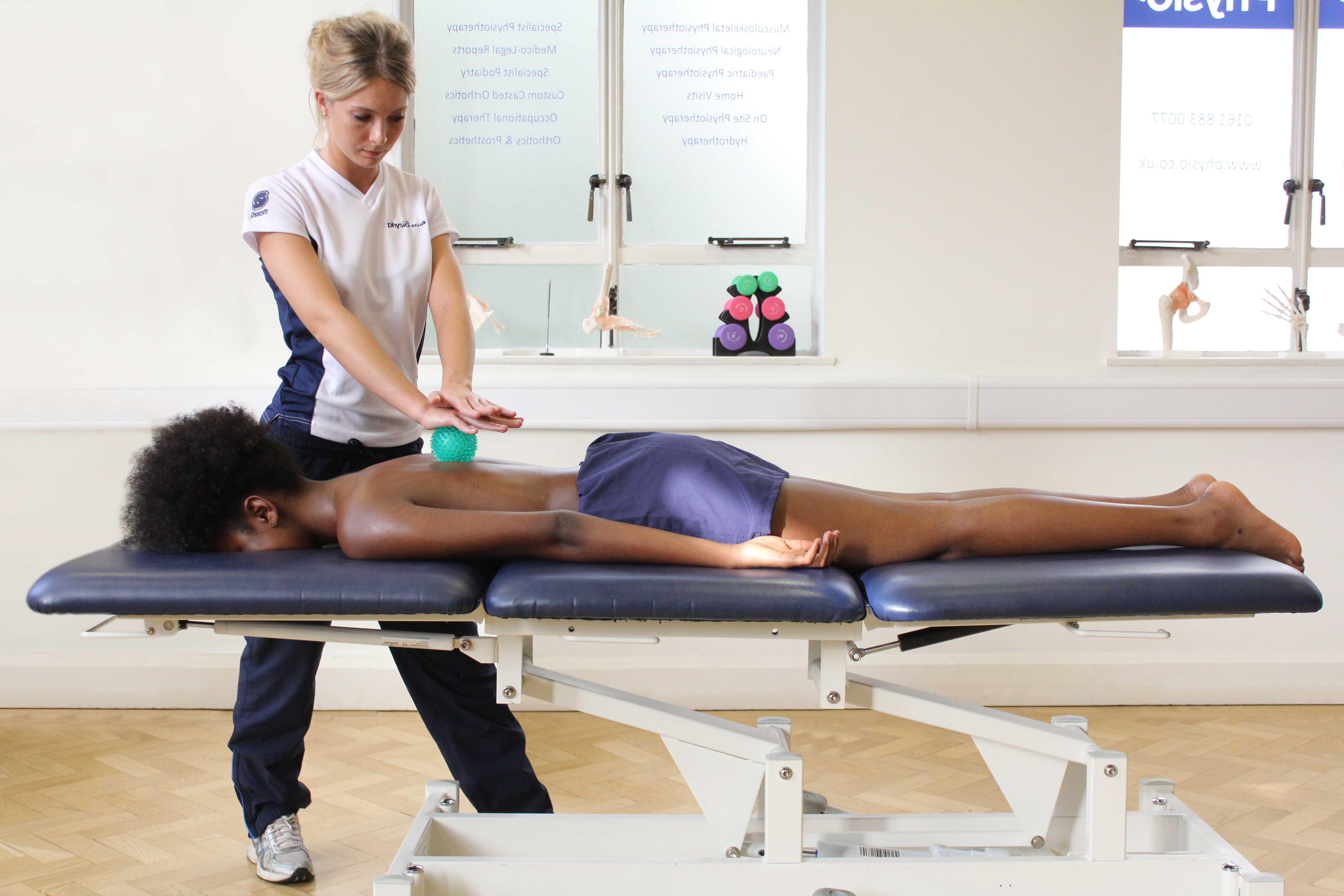 Soft tissue massage of the upper back muscles using a therapy aid