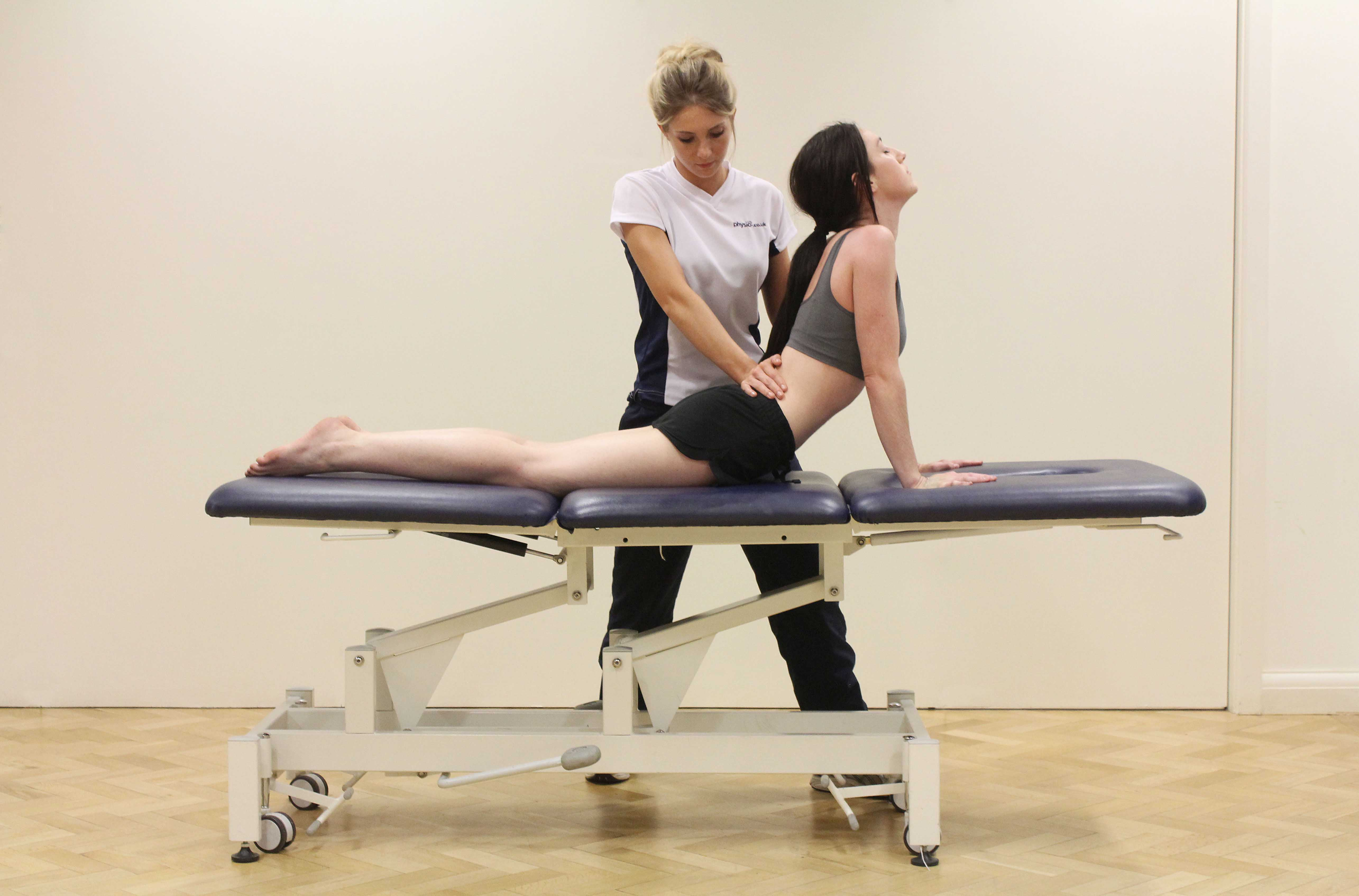 Stretches and compression of the lower back structures by therapist to relive painful symptoms