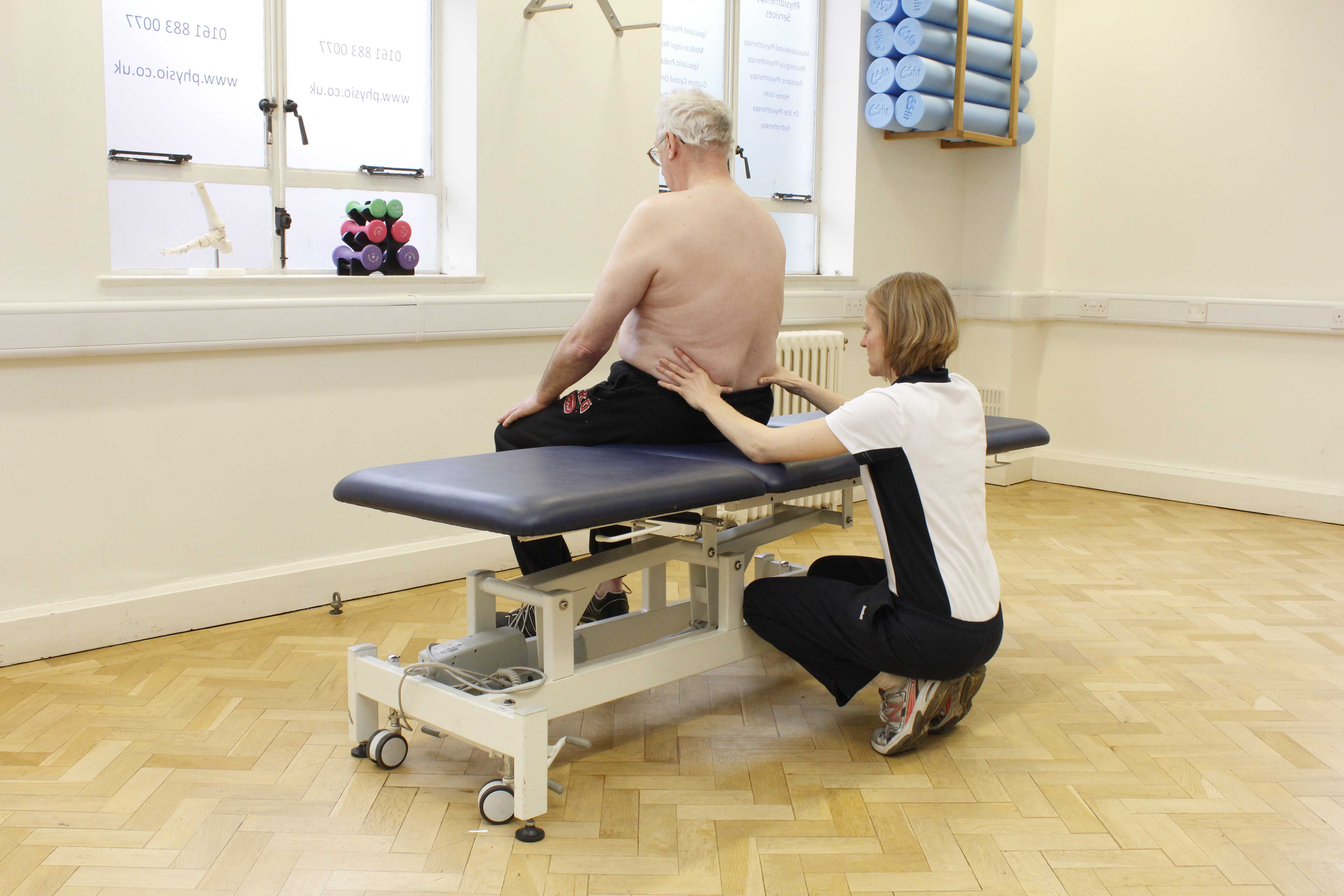 Lower back assessment by physiotherapist to identify cause of muscular spasm