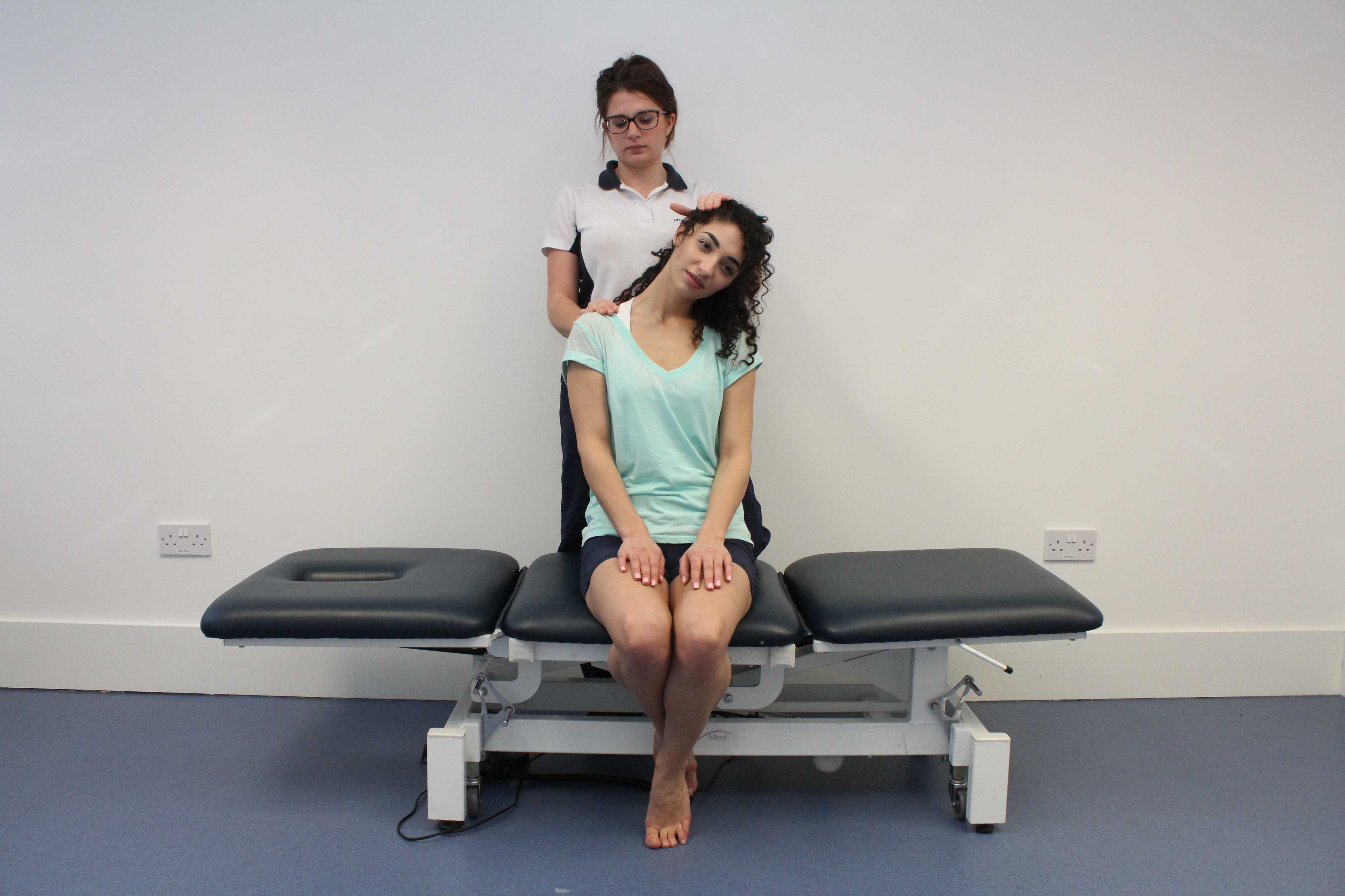 Stretches applied to the trapezius muscle and connective tissues in the neck by physiotherapist