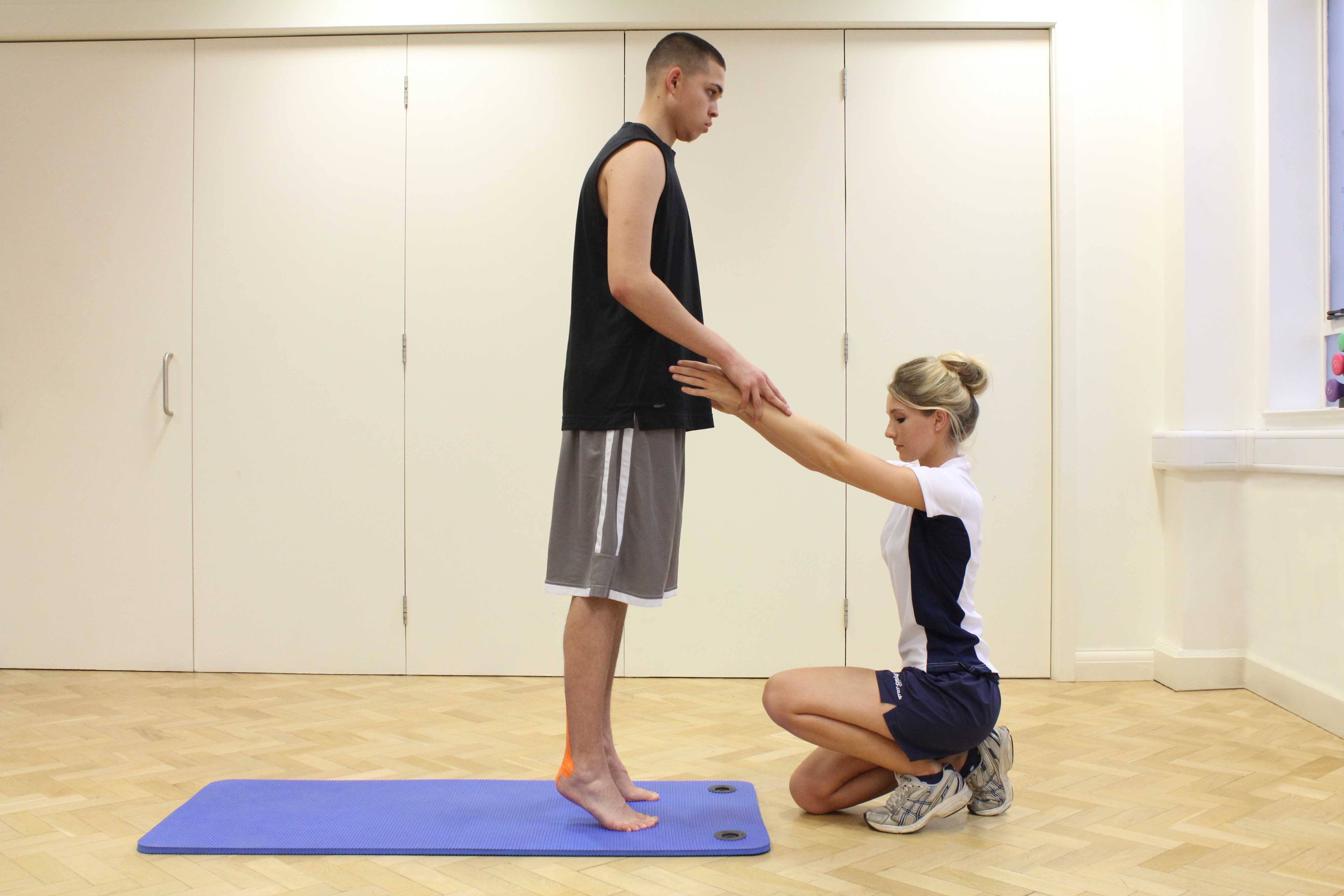 Progressive ankle strengthening exercises, with tape applied, supervised by therapist