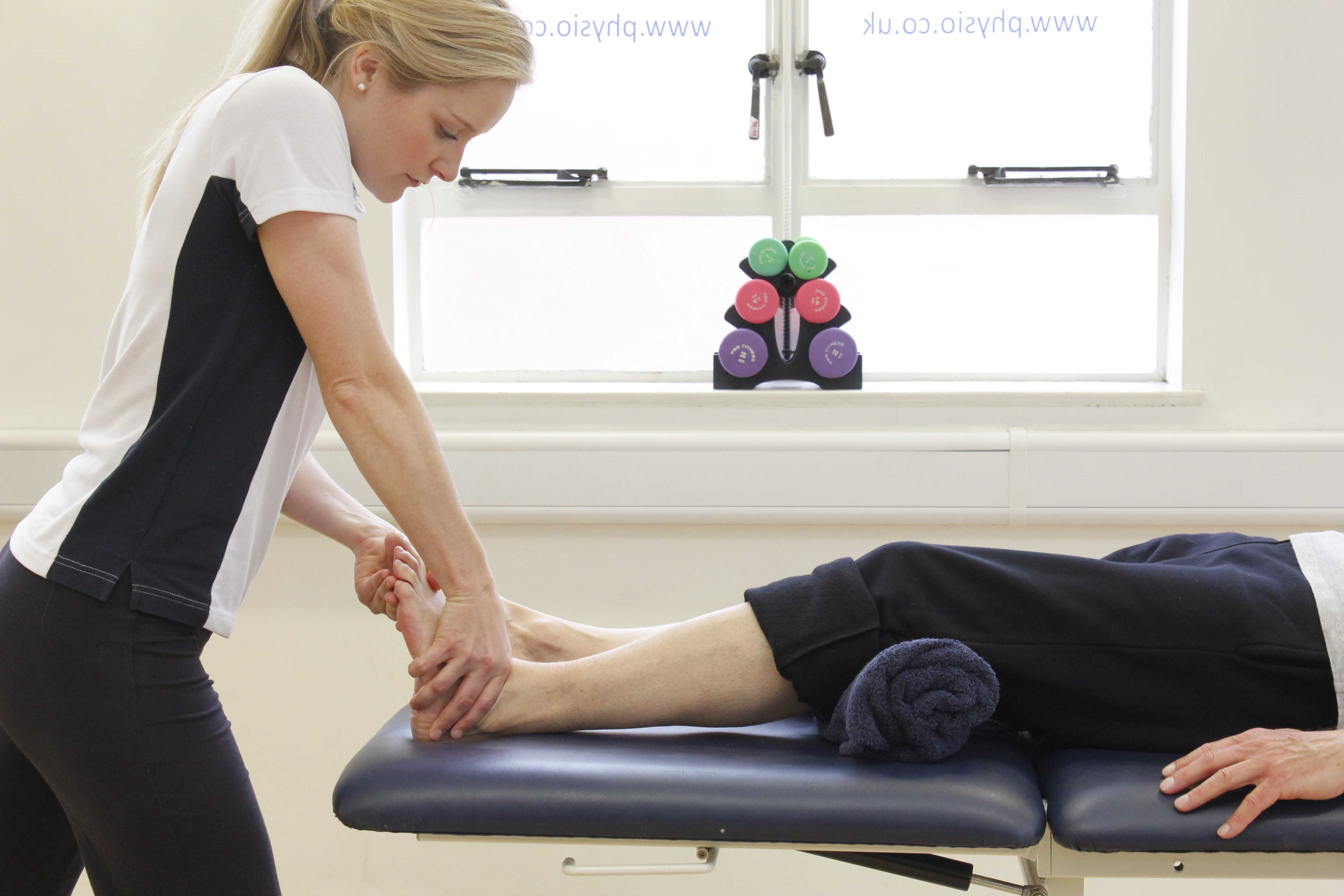 Effluage massage applied to the ankle joint to disperse swelling in the soft tissues