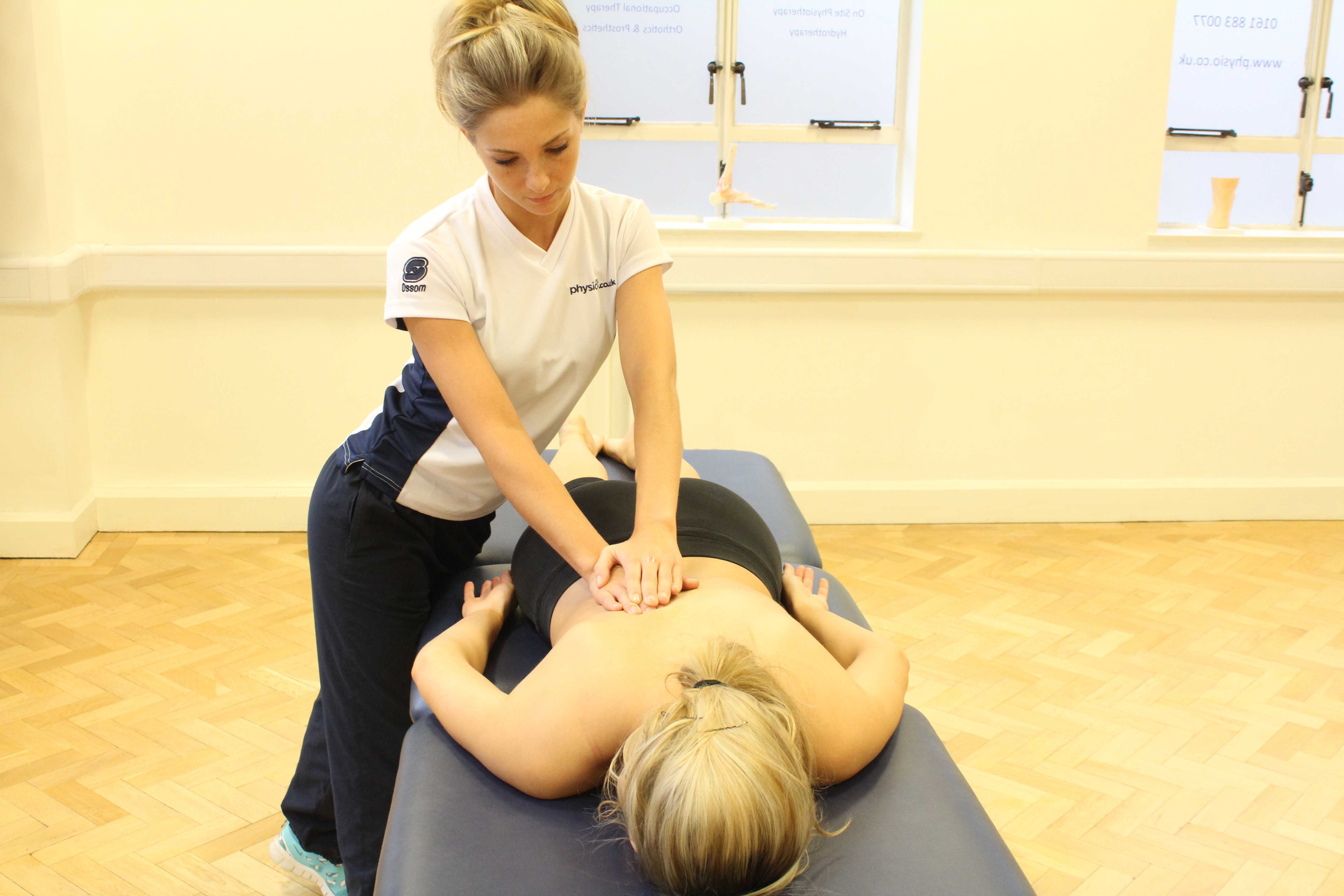 Therapeutic massage focusing on laissimus and rhomboid muscles