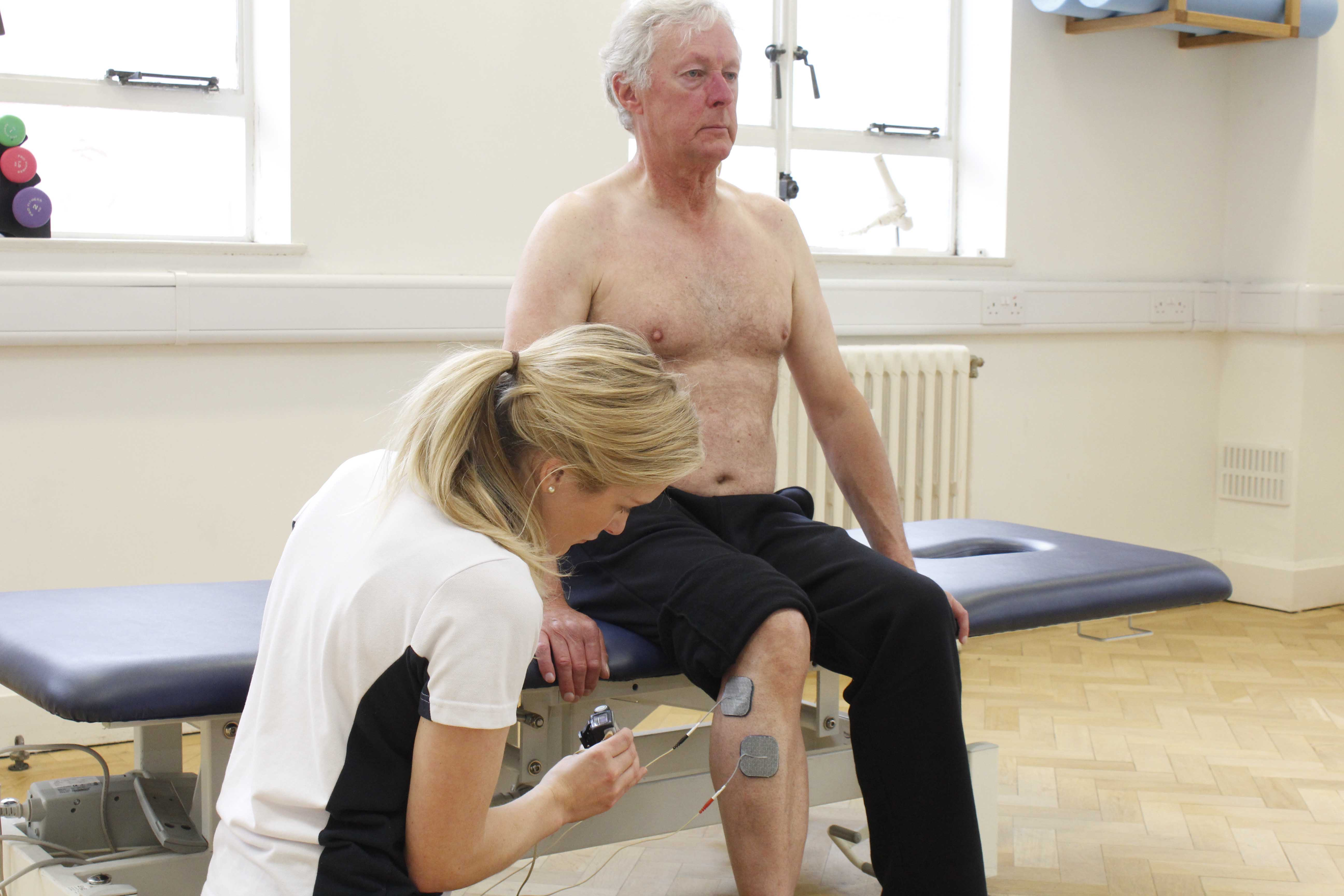 Specialist physiotherapist applying electrical stimulaton to alleviate pain and stiffness