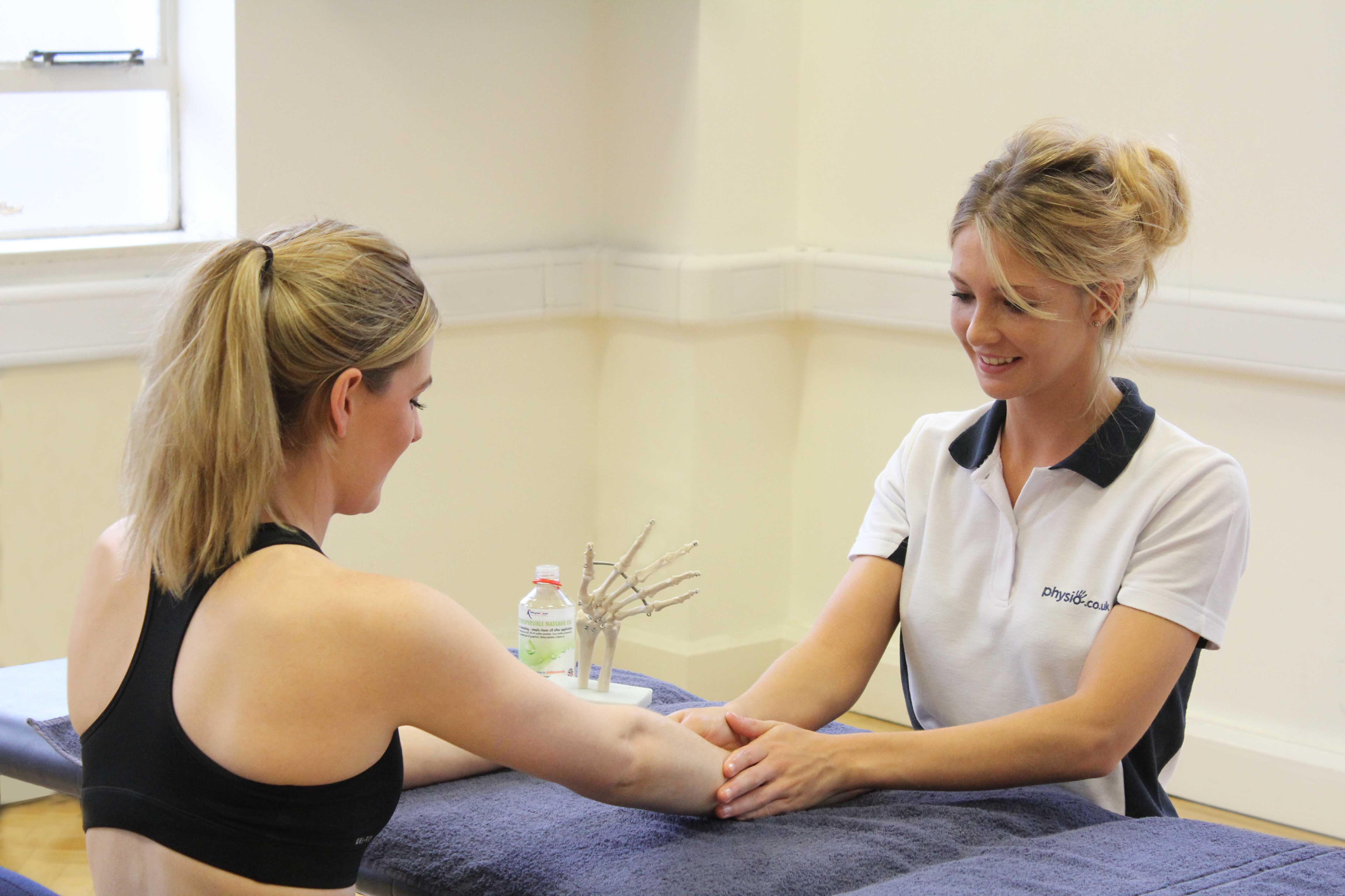 Therapist applying soft tissue massage to the forearm and wrist