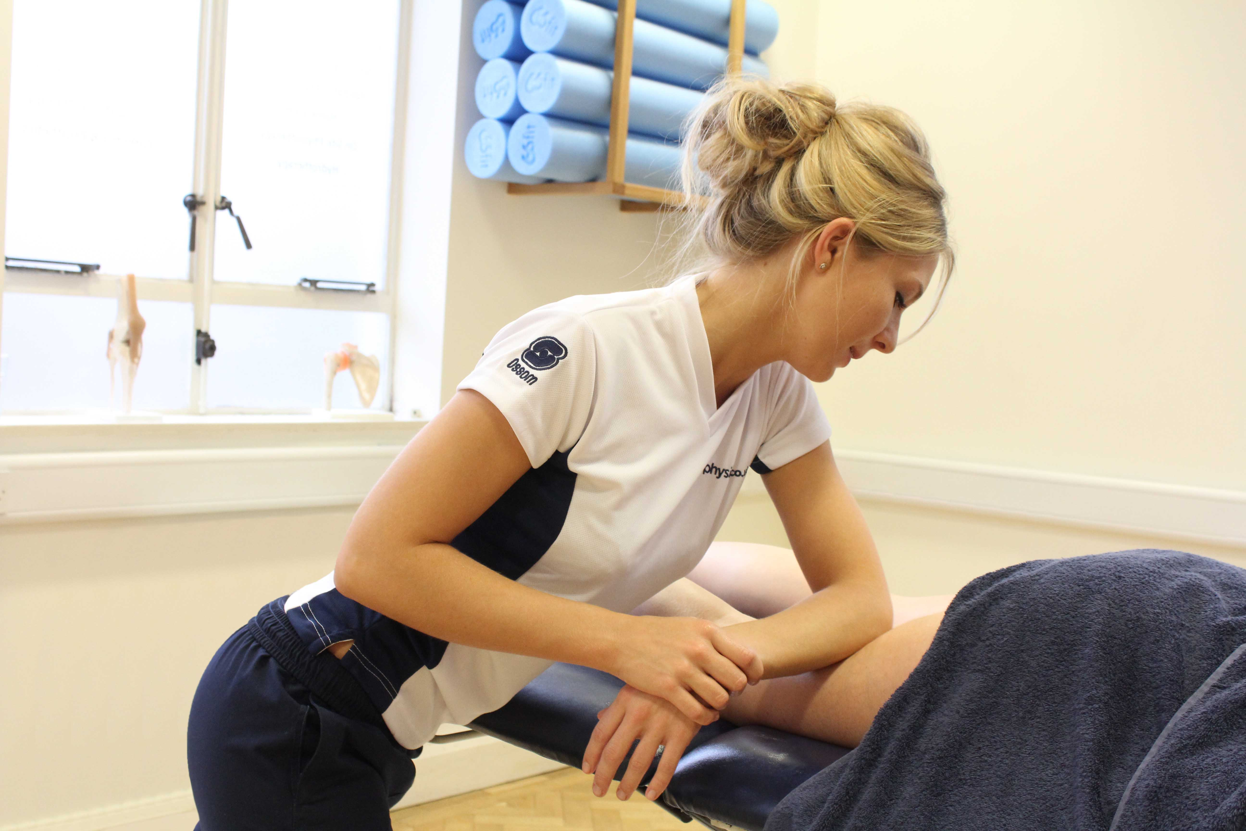 Rolling soft tissue massage of the quadriceps muscles by a specialist MSK therapist