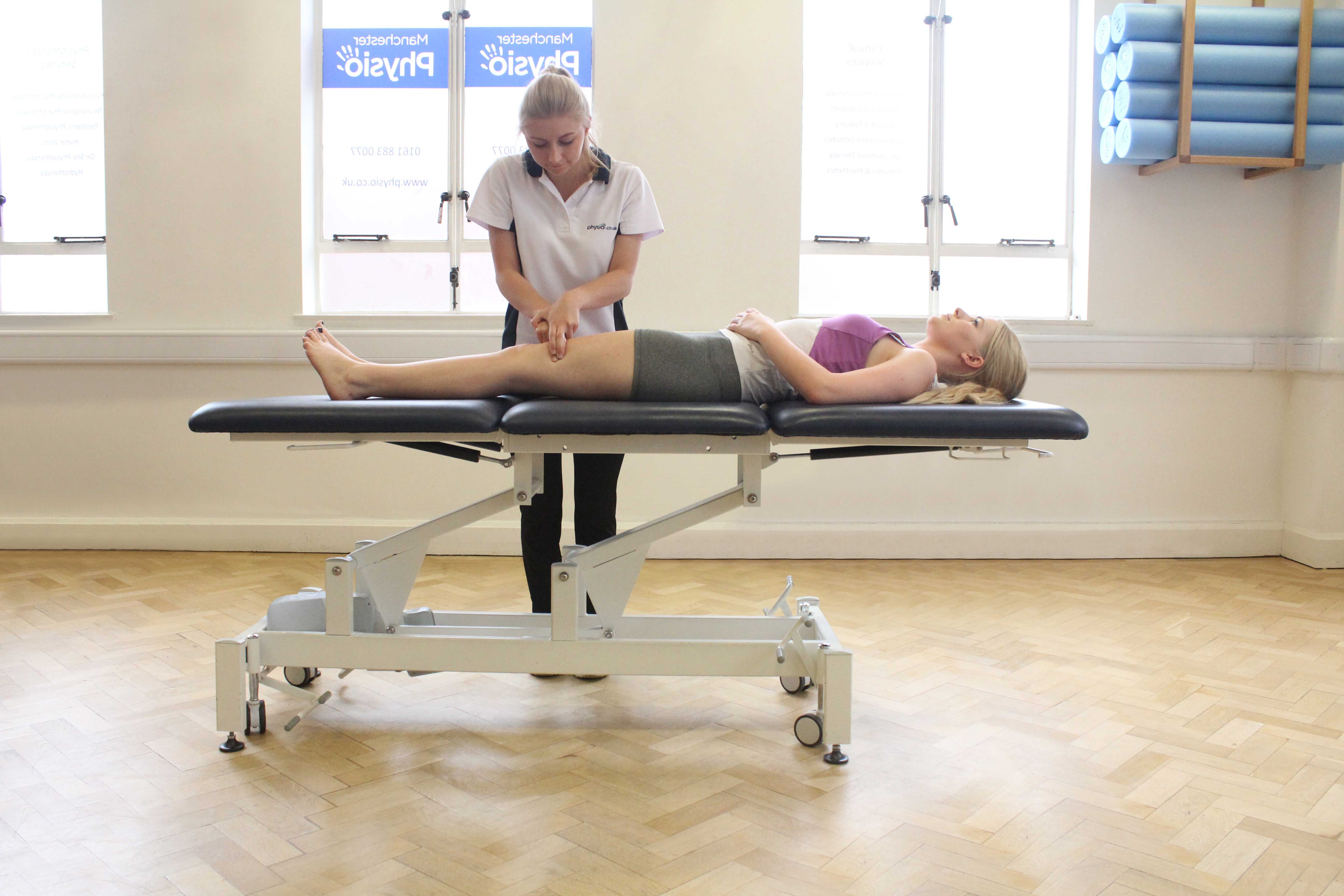 Hacking percussion massage of the quadricep muscles by a specialist MSK therapist