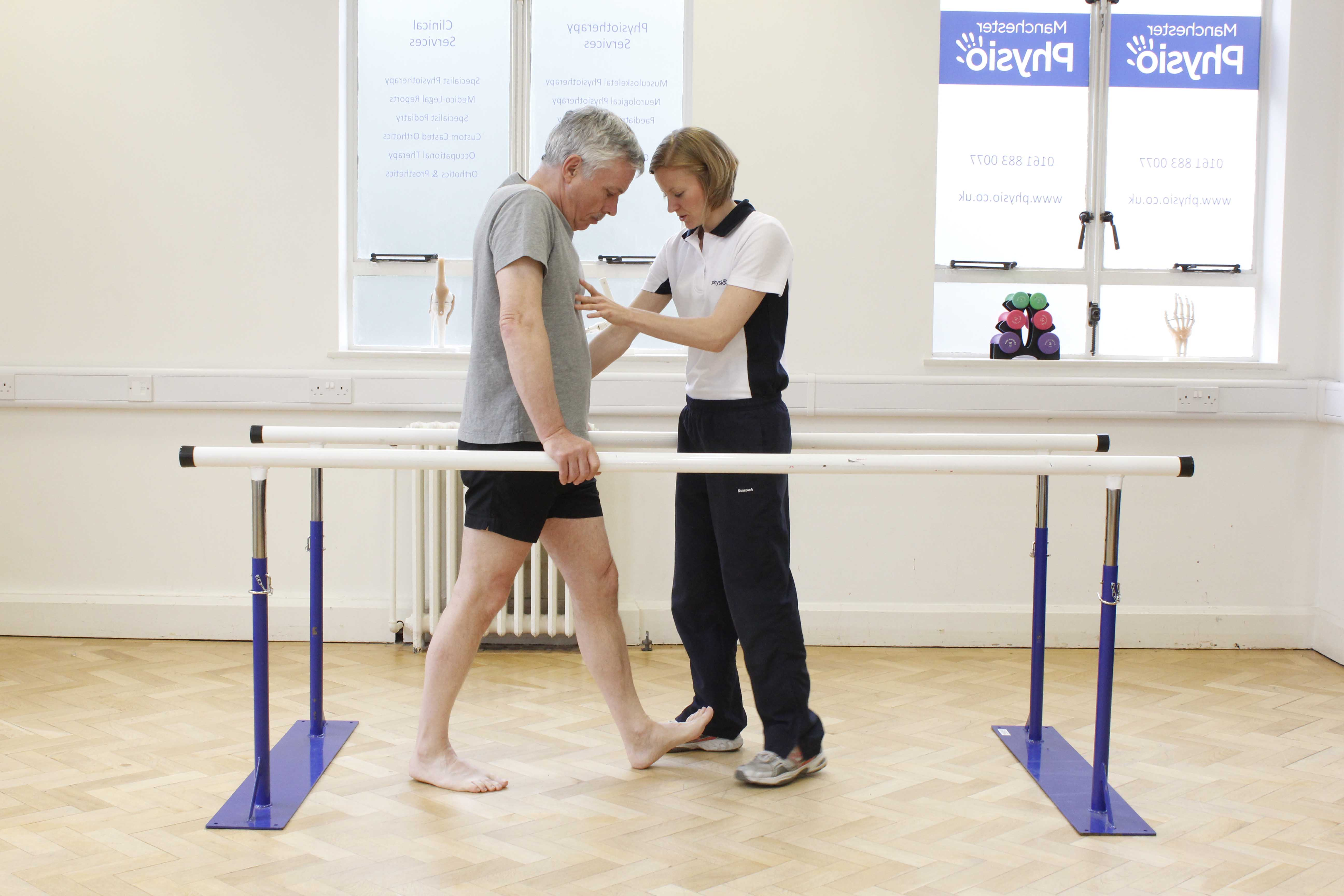 Gait re-education mobility exercises between the parallel bars under supervision of a physiotherapist