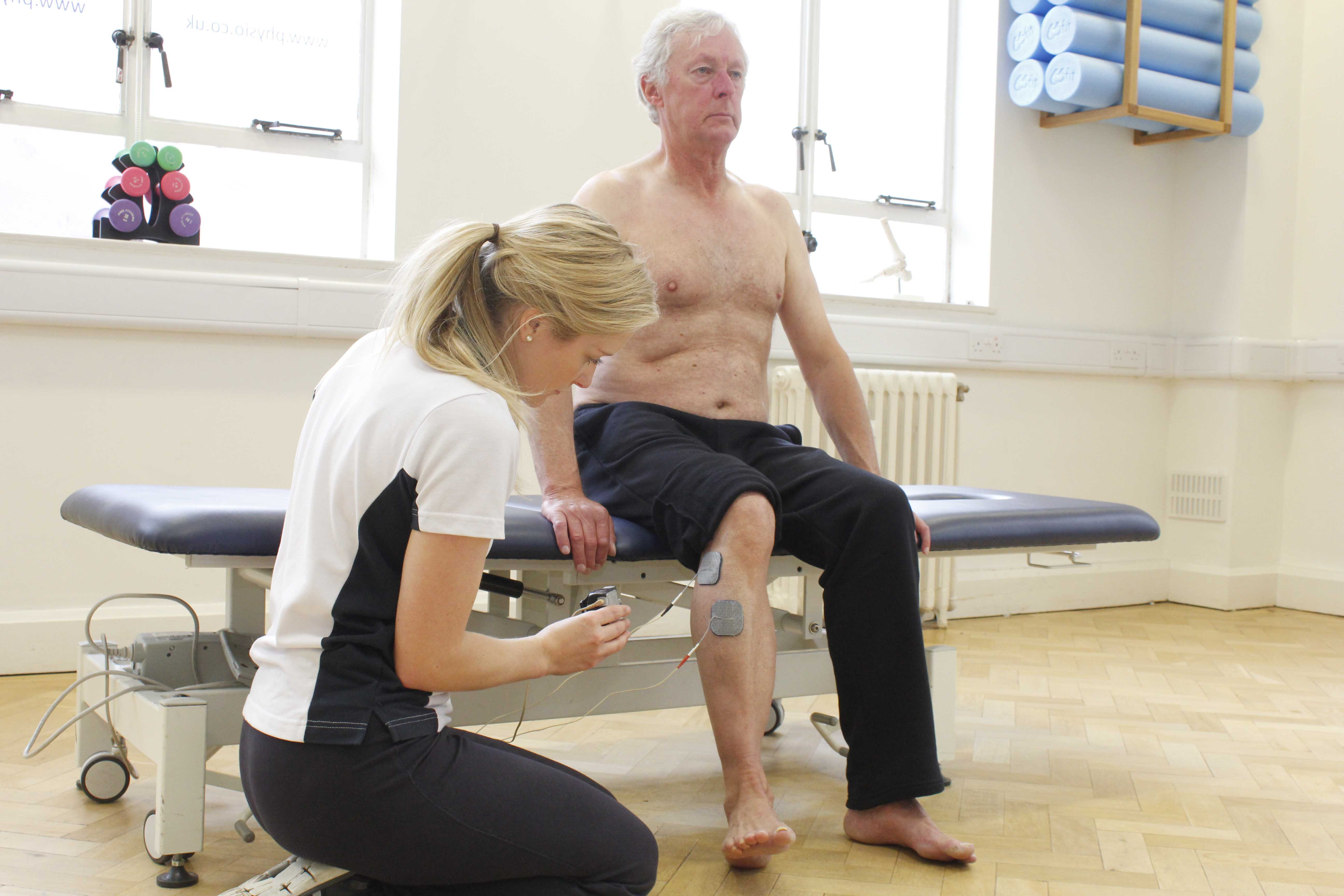 Physiotherapist applying Functional Electrical Stimulation pads to ankle flexor muscles