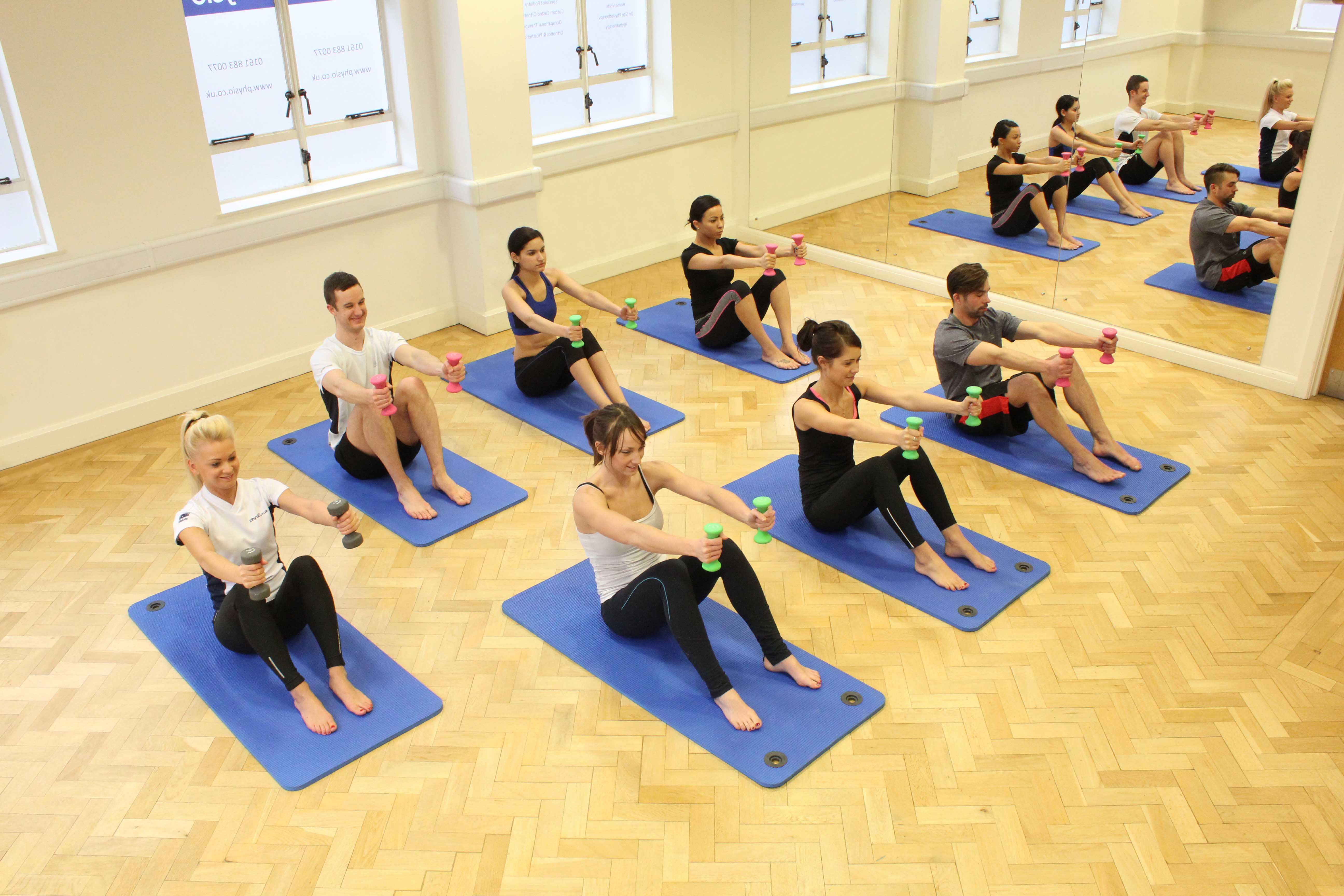 Physiotherapist led pilates class using foam rolls